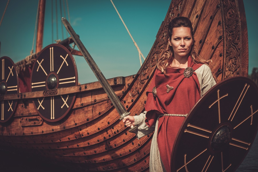 Viking woman wearing traditional clothes near a ship