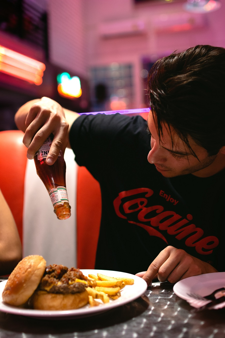 Man pouring sauce on burger and fries